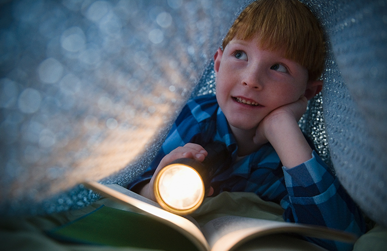 Young child hiding reading a book by torchlight