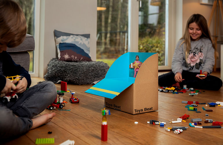 Children playing indoors with toys, Lego and a box