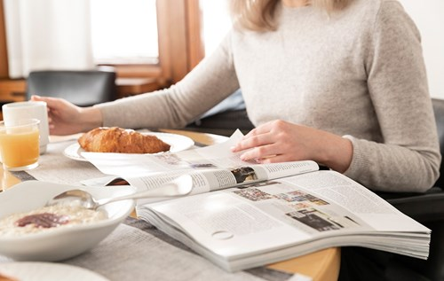 reading a newspaper over breakfast table