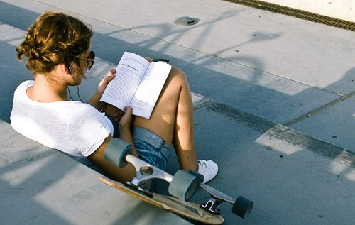 Young woman reading a paperback book on steps